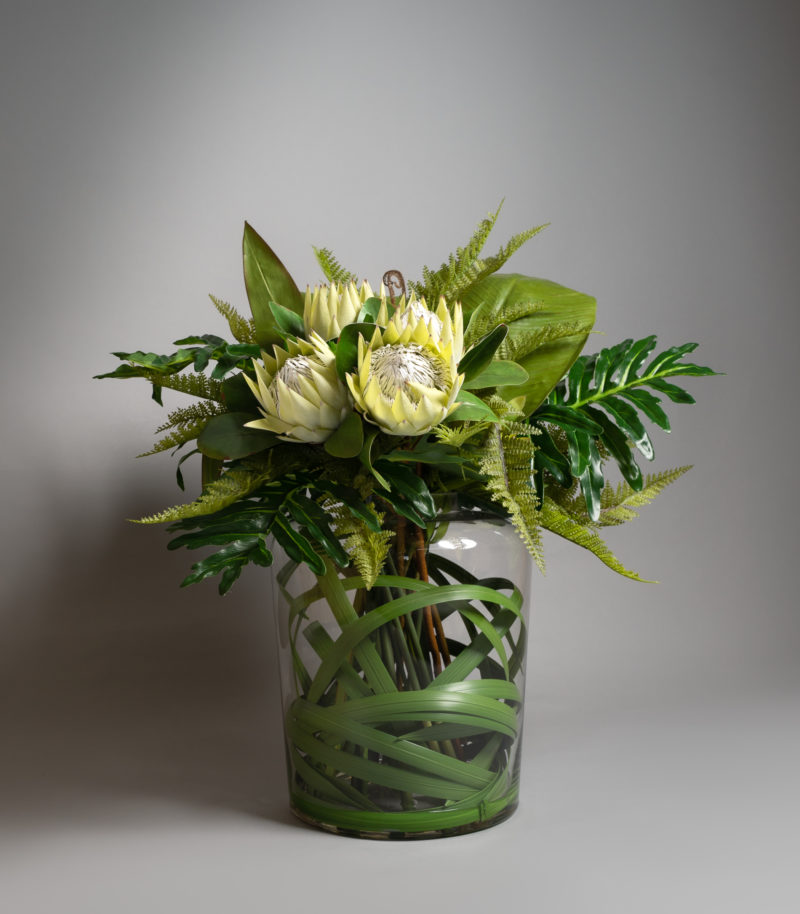 Green protea in glass vase