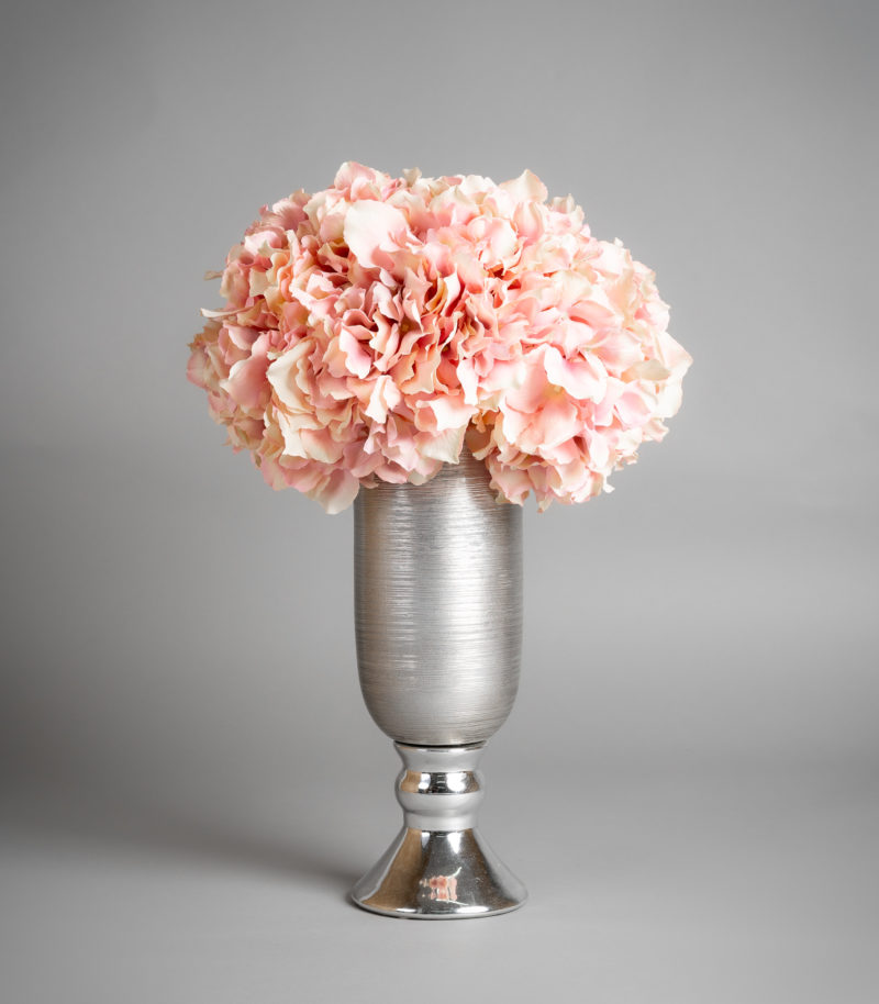 Pink hydrangea in tall silver vase