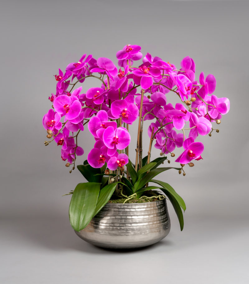 Pink orchid arrangement in silver bowl